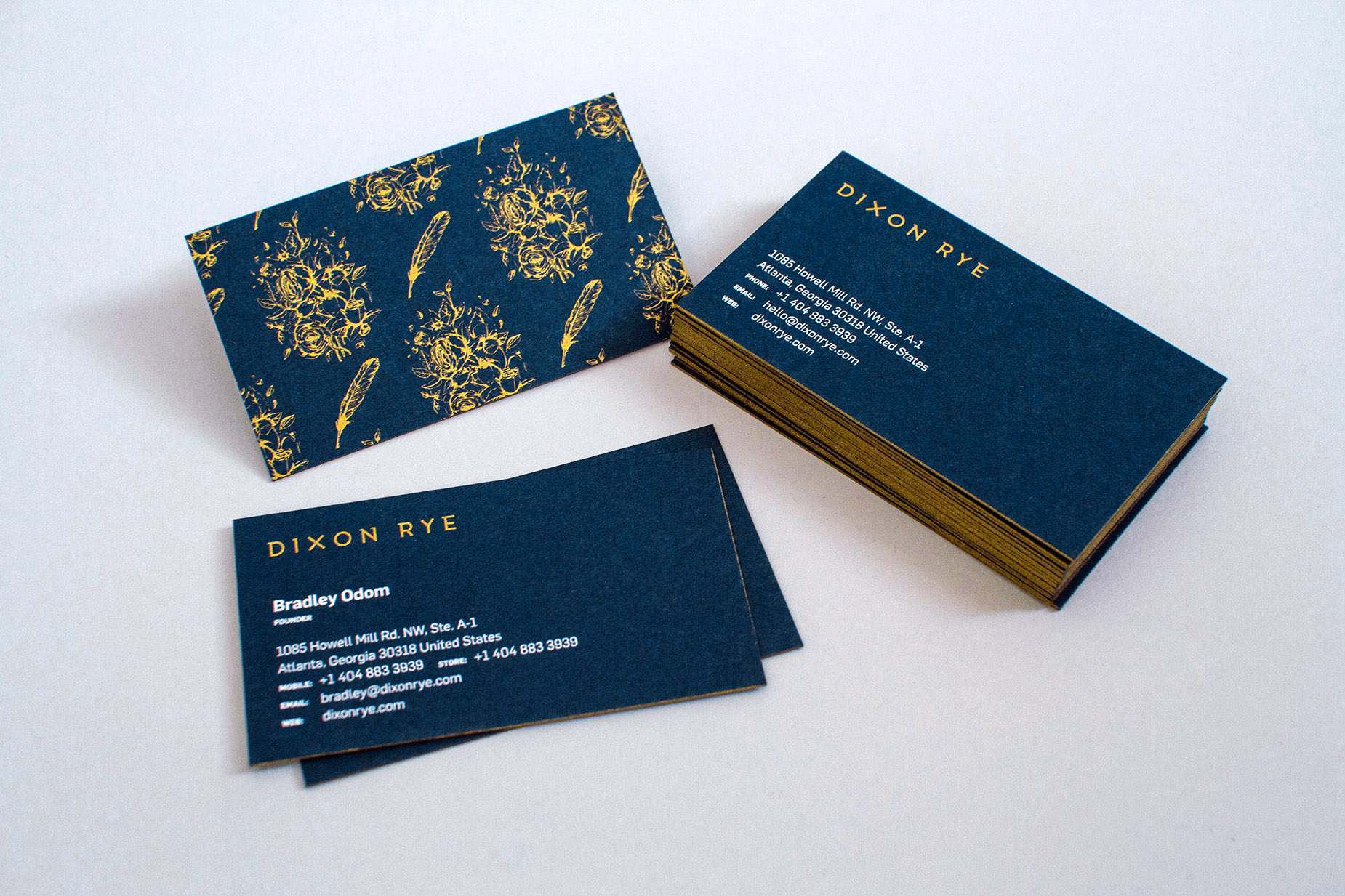 Thick French Paper Nightshift Blue navy business cards with gold edge painted sides, and the Dixon Rye logo silk screen printed in a metallic gold Pantone.