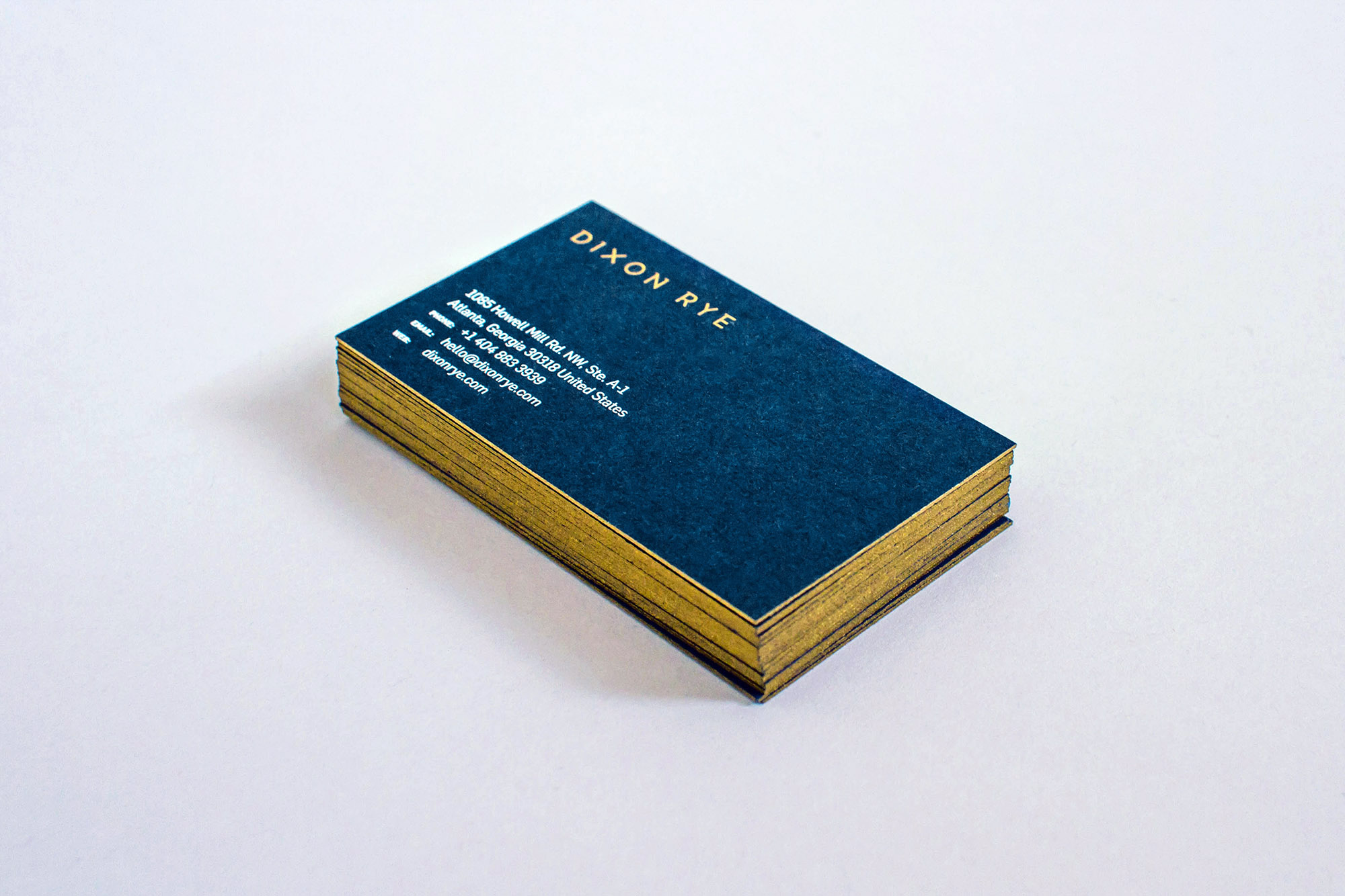 Stack of retail store business cards with Dixon Rye logo design screen printed in gold metallic Pantone on navy paper, with store info in white ink, and gold edge painting along the sides.