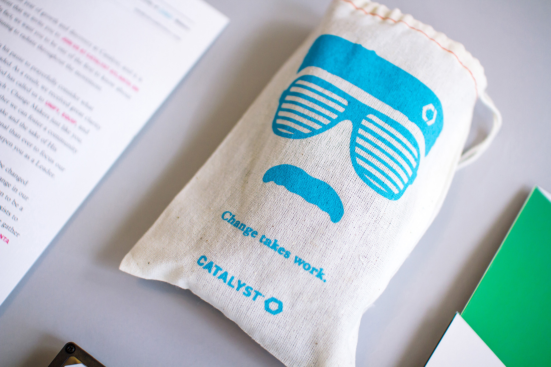 Stunner shades, mustache, and headband illustration that reads Change takes work on a custom screen printed linen cotton drawstring bag for Catalyst Conference 2014.