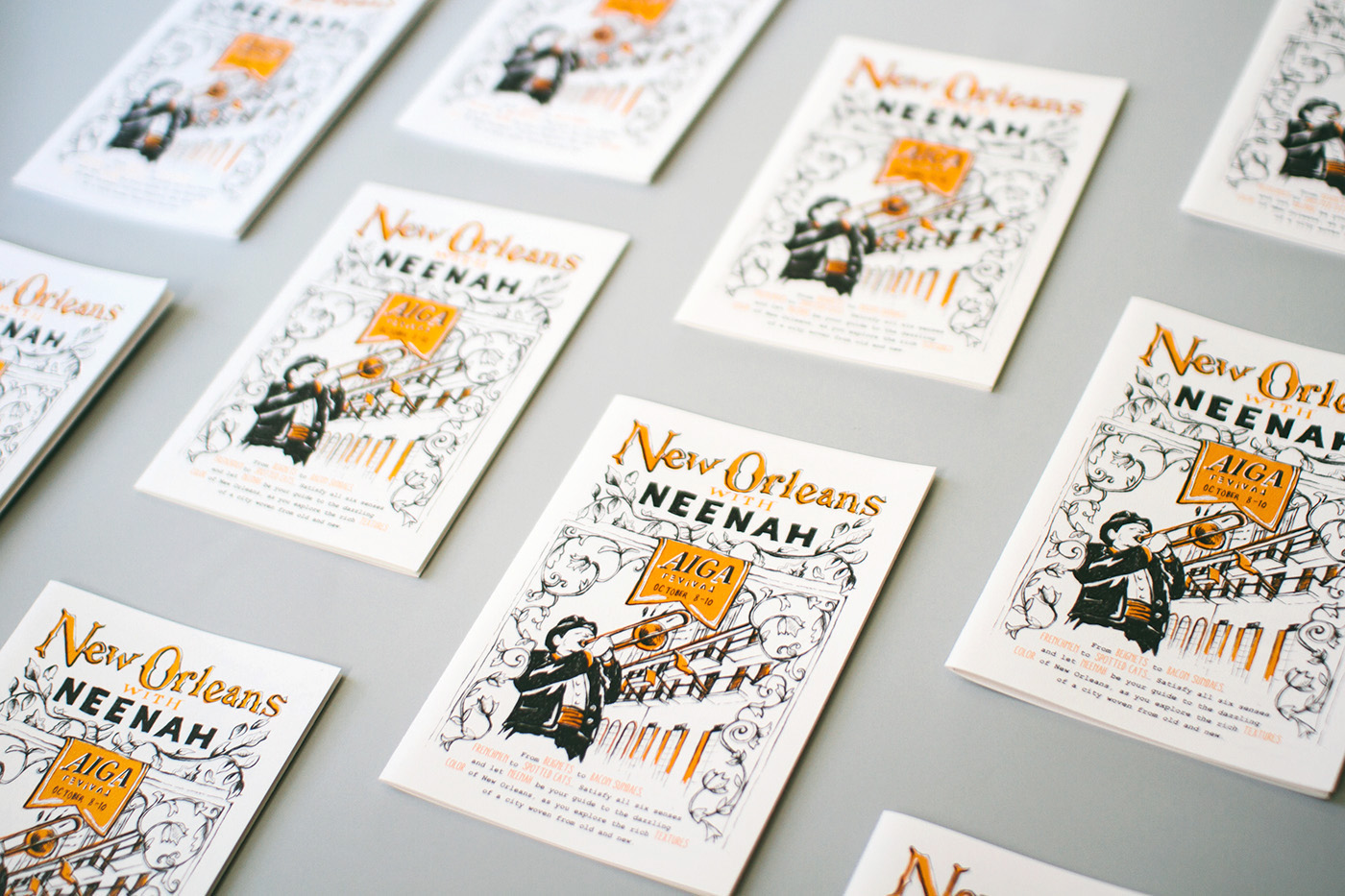 Cover illustration and design of New Orleans with Neenah, for Neenah Paper at the AIGA Conference 2015. A man in a suit plays the trombone with hand-drawn floral borders around him and a New Orleans balcony in the background.