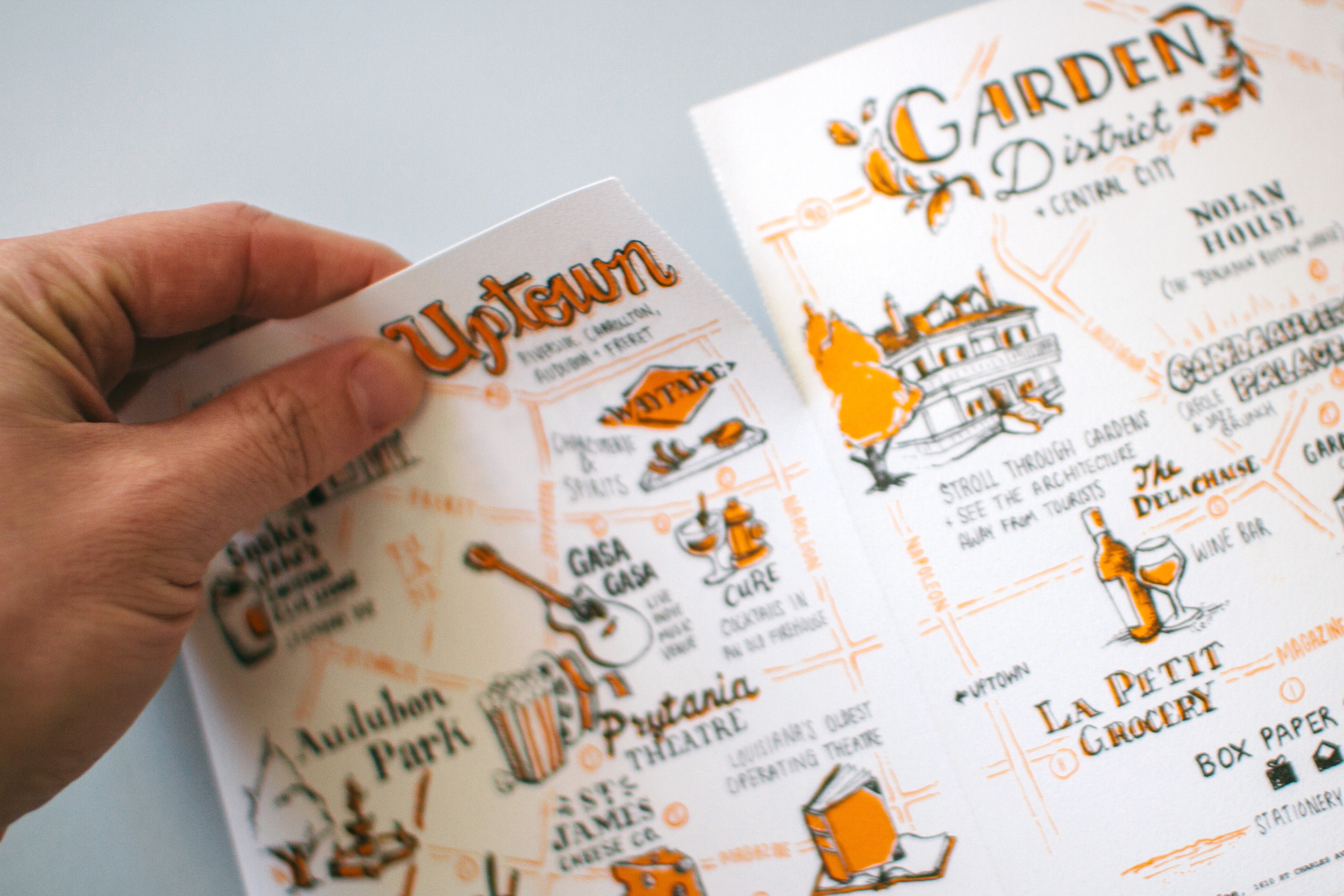 The perforated edge between each neighborhood map allows the viewer to separate each one as an individual postcard or print. Here, someone tears the Uptown card off of the Garden District neighborhood guide.