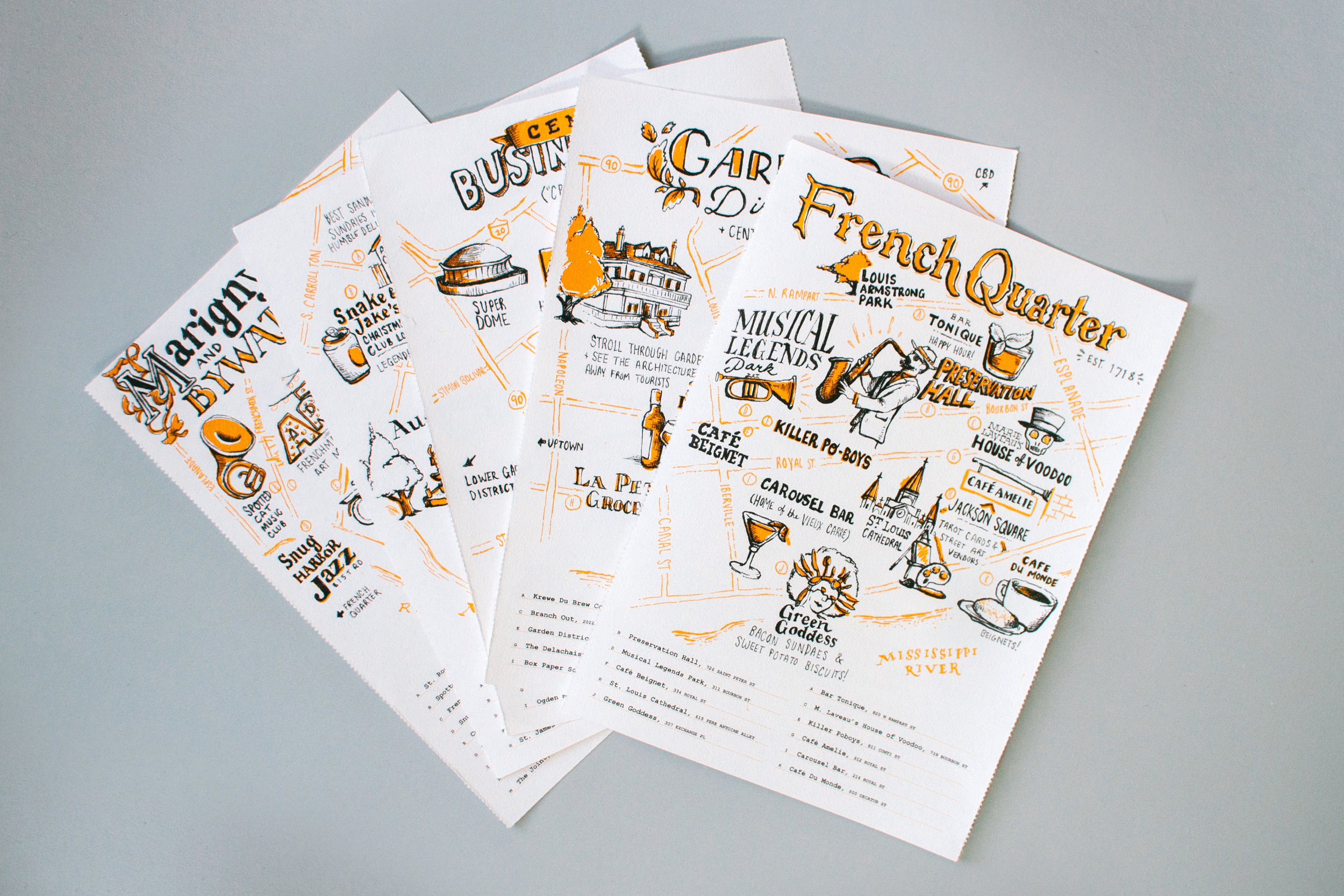 All of the New Orleans with Neenah Paper illustrated neighborhood guides separated as individual prints are fanned out on top of each other. On top is the French Quarter.