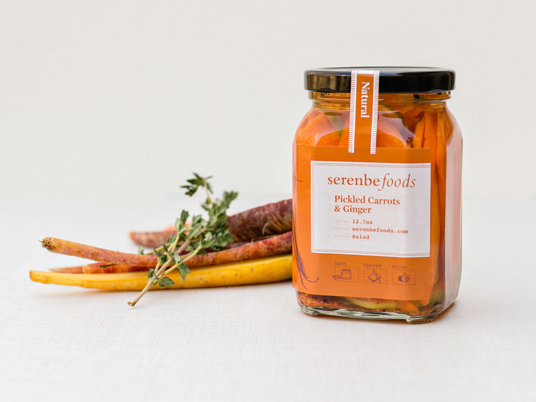 Carrots lay behind jar of pickled carrots and ginger, featuring the label design and brand identity and logo for Serenbe Foods line of jams and consumer packaged goods.
