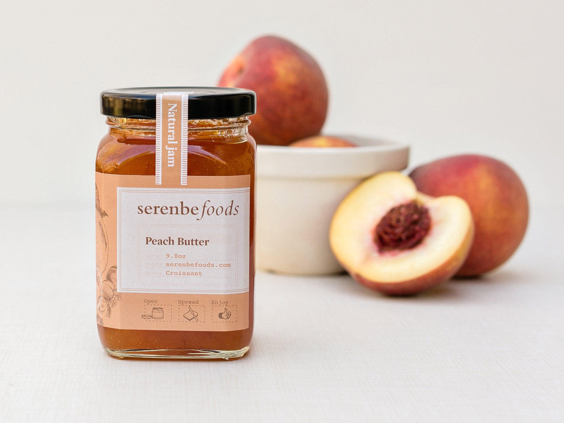 A bowl of peaches sit behind a jar of Serenbe Foods all natural Peach Butter jam, showing the label and brand identity packaging design.
