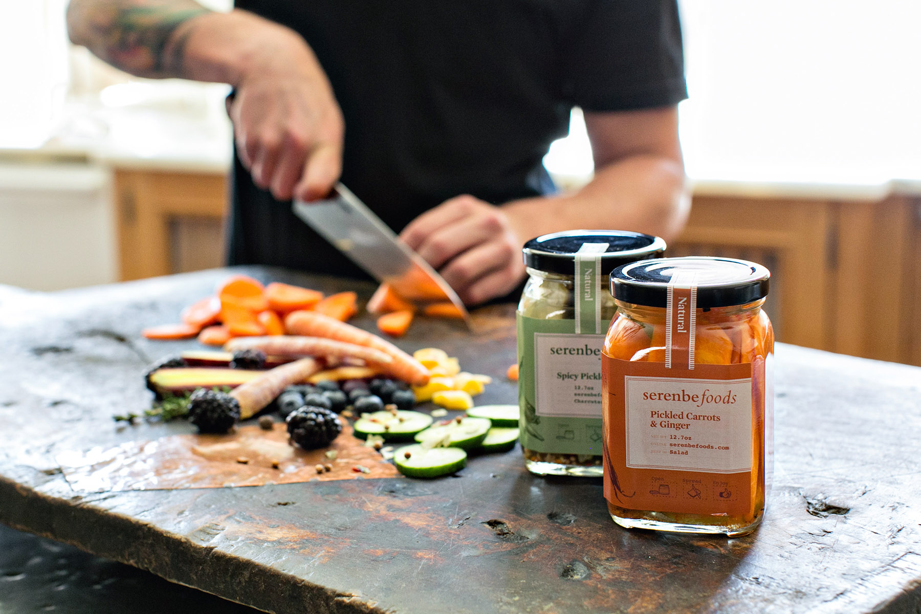Man with knife cuts carrots and pickles in the background, with natural jelly and jam jars of Serenbe Foods in the foreground, designed by Russell Shaw.