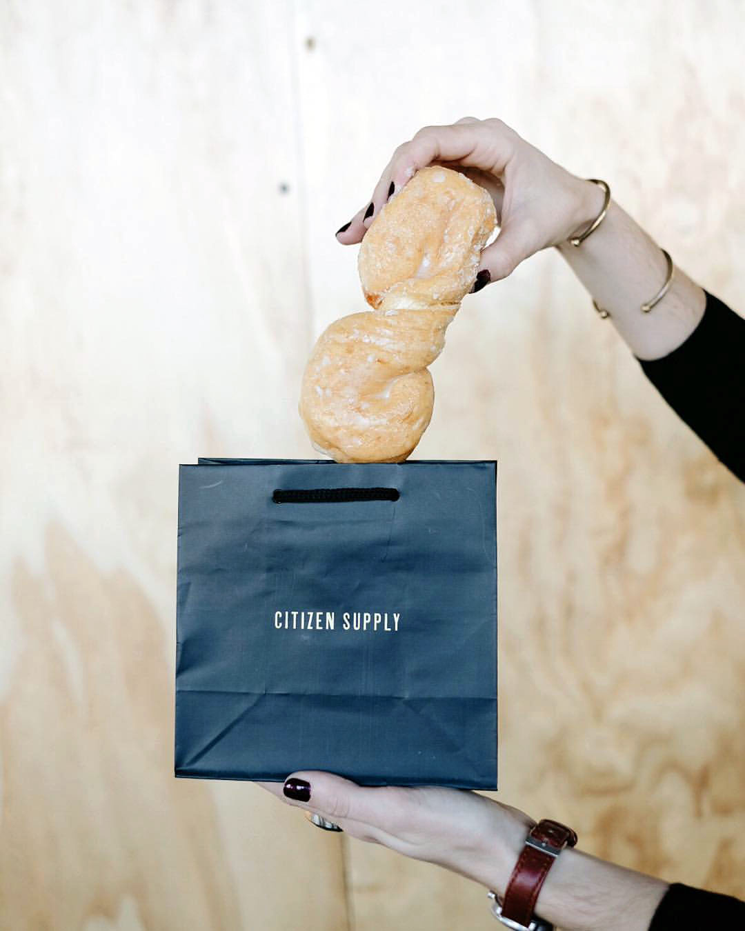 Citizen Supply retail packaging and store bags show the branding and logo design in gold letters on black bag and a girl pulling out a donut.