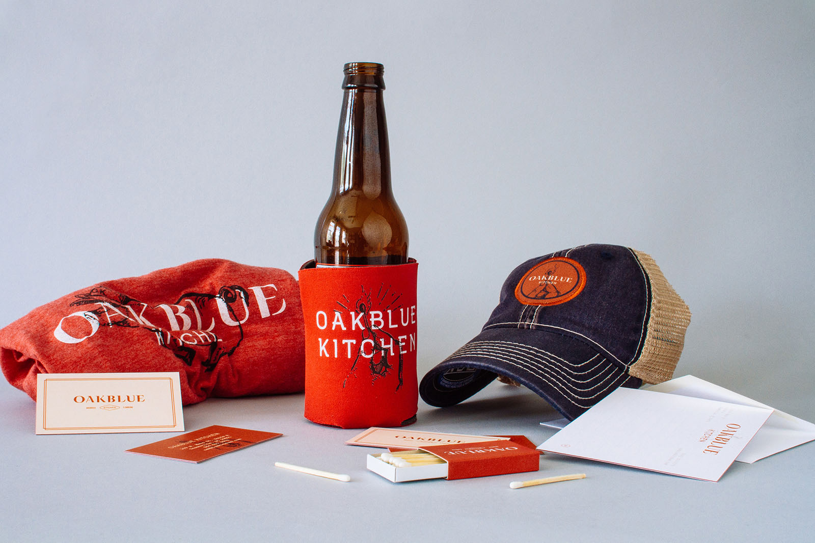 Samples of Oakblue Kitchen restaurant branding collateral design, with a red t shirt, koozie for beer, business cards, hat, matches and notecards.