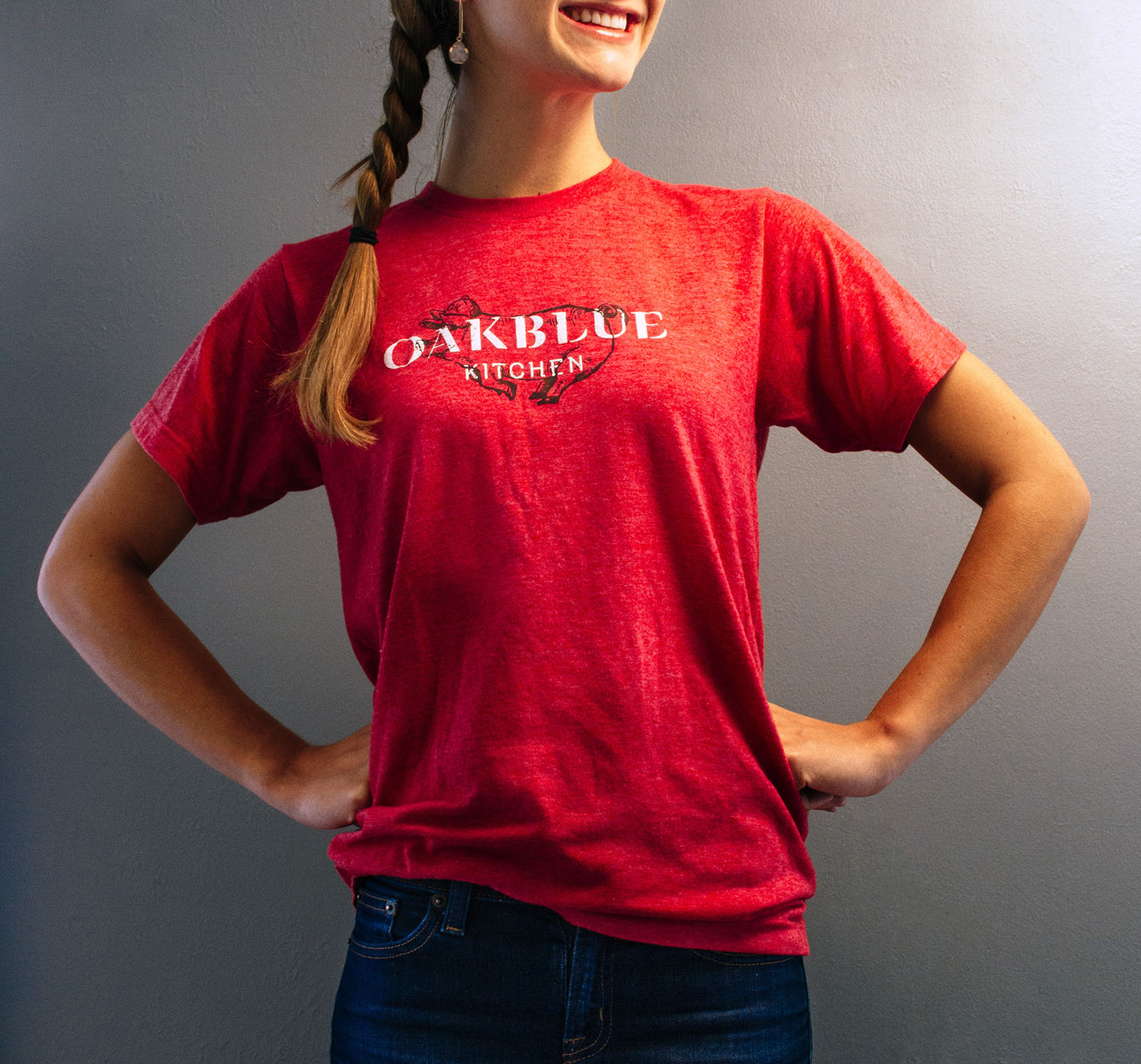 A woman wears the t shirt design for restaurant Oakblue Kitchen with custom logo in white over hand drawn barbecue pig illustration on a heathered textured red shirt.