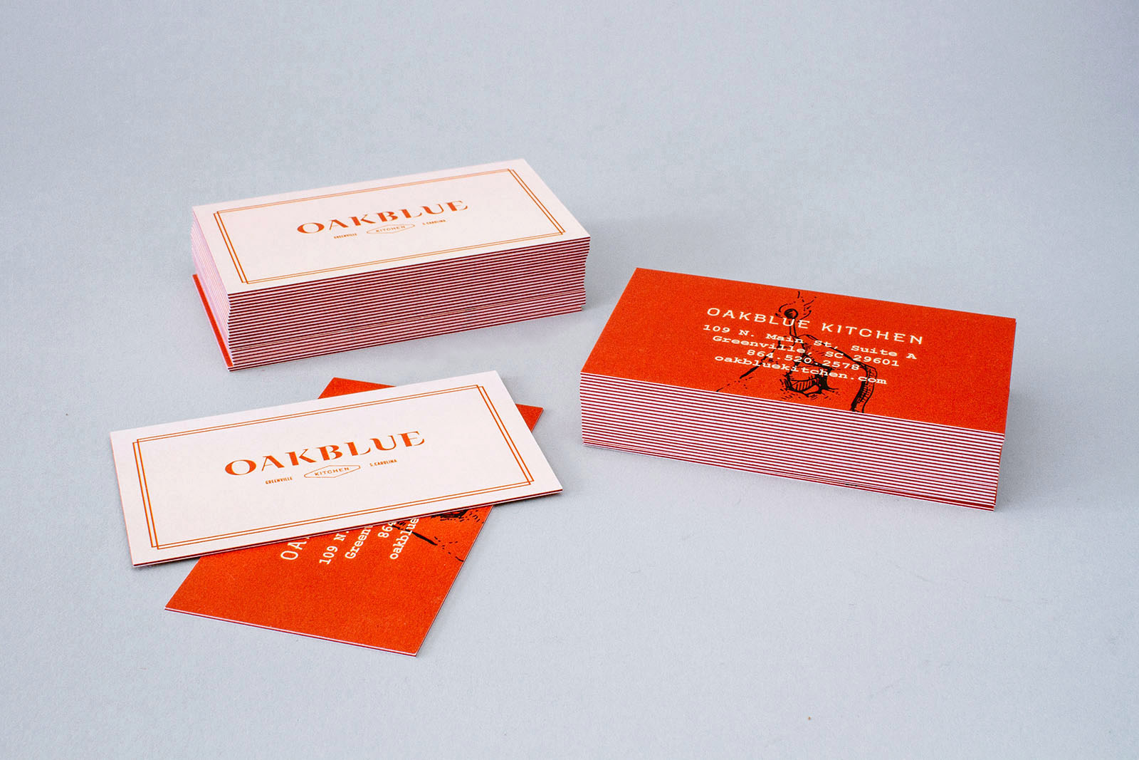 Stack of Oakblue Kitchen restaurant business cards, with red side seam.