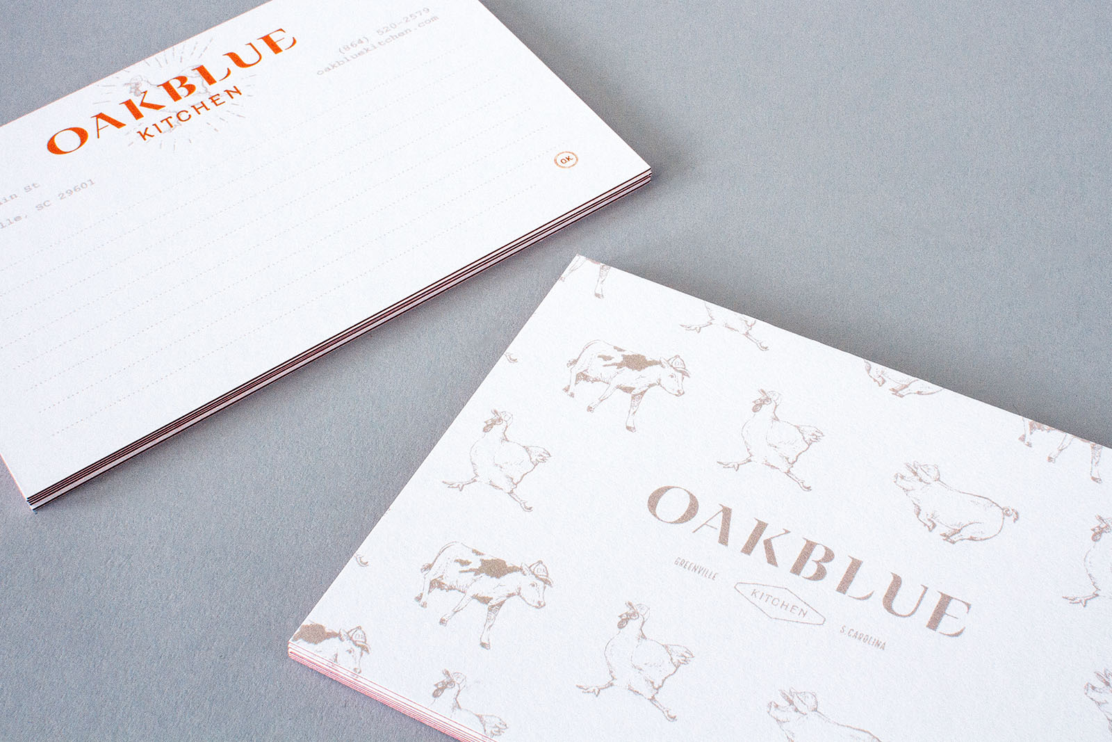 Stack of Oakblue Kitchen restaurant notecards, part of the brand collateral and stationery, with red side seam and hand drawn illustrations of cow, chicken and pig on the back of each card.
