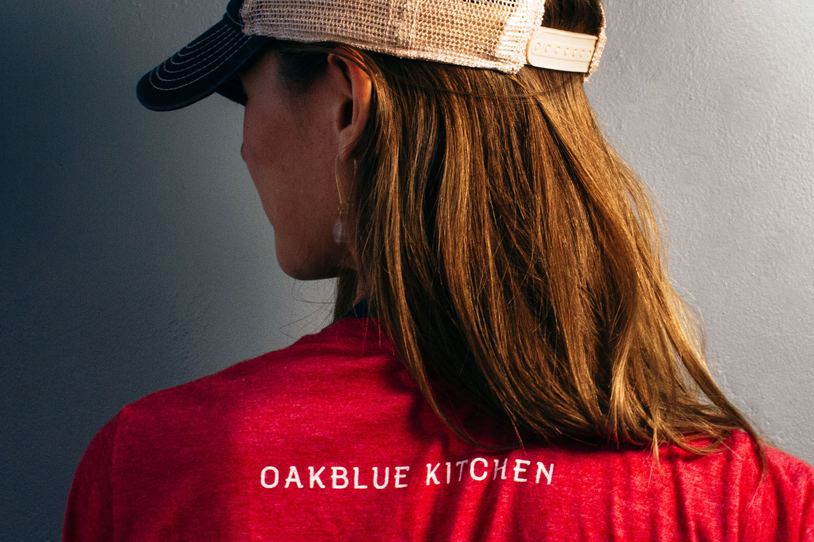 Woman modeling the Oakblue Kitchen restaurant hat and shirt design. On the top back of shoulder of shirt, the barbecue joint name is in the custom designed font and typeface made for the brand.