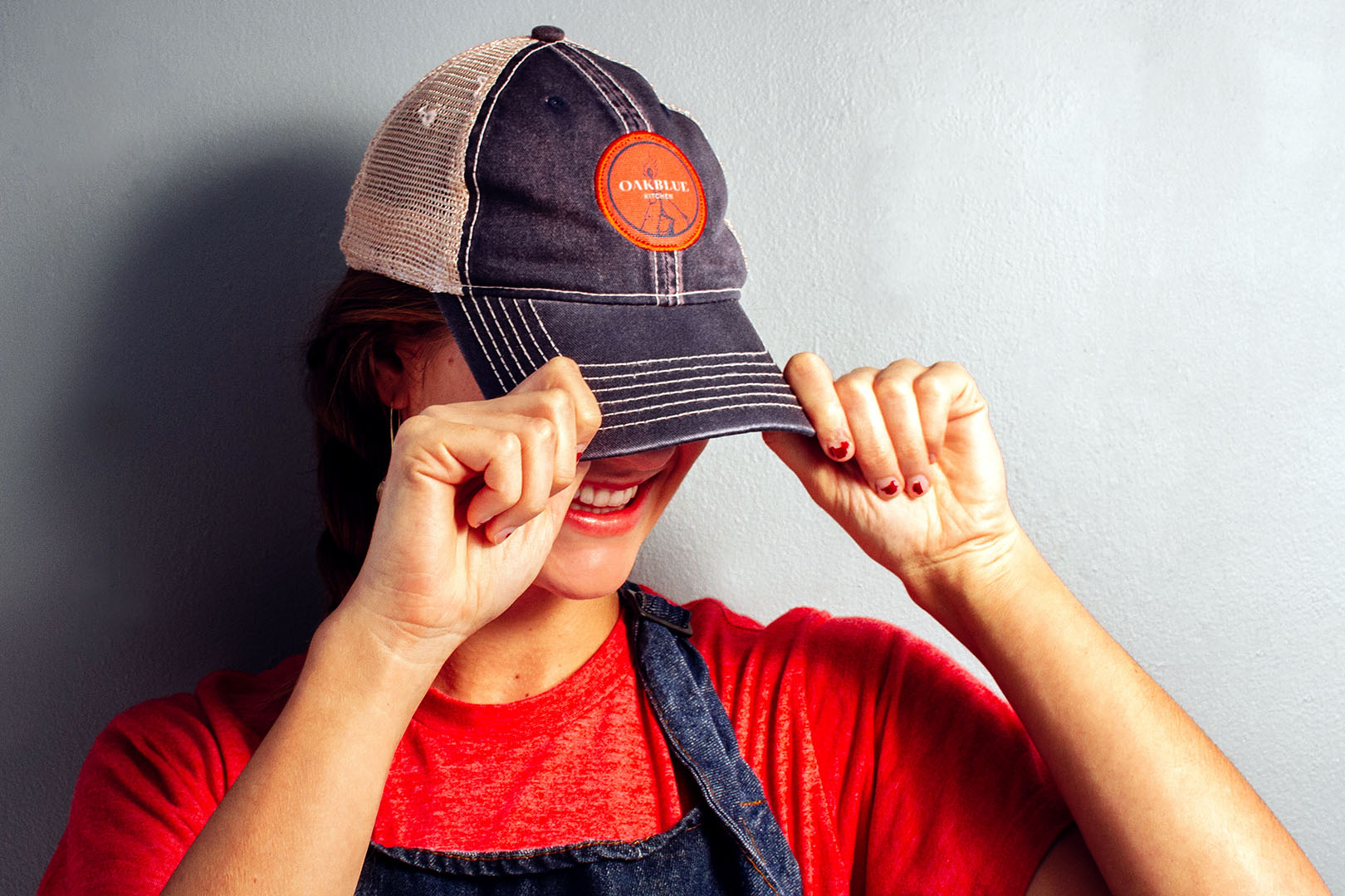 Woman pulls navy trucker hat over her face, revealing the embroidered patch for the restaurant branding and logo design on the front of the ball cap.