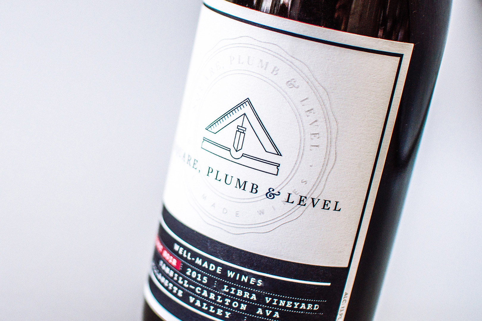 Detail of the front of the pinot noir run of Square Plumb and Level wine label designs show the logo icon and the seal embossed on the cover.
