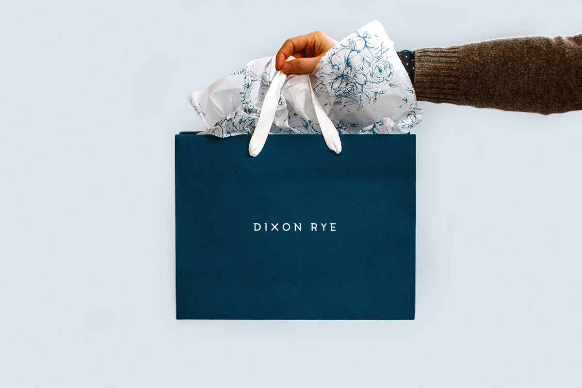 Dixon Rye's packaging design features a navy paper bag with white handle and a custom floral pattern on white tissue paper.