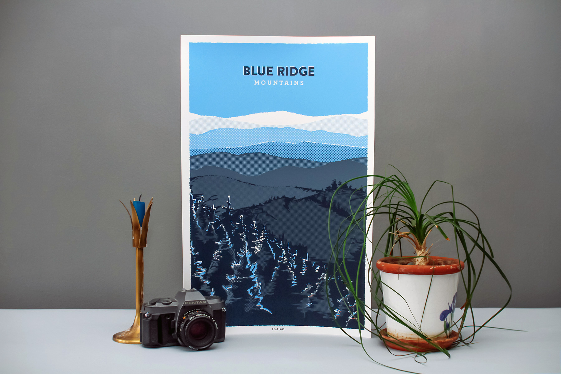 Illustrated poster and art print of the Blue Ridge Mountains. Features tree silhouettes in the foreground and rolling blue and gray mountains and hills into the horizon. Created by graphic artist and designer Russell Shaw for Bearings Guide.