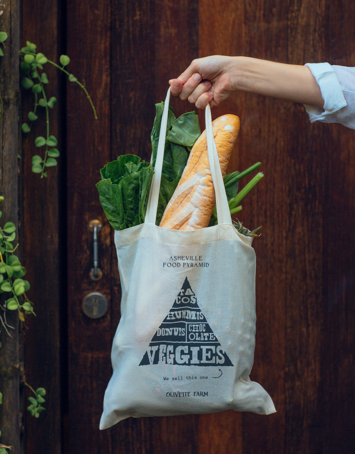"Asheville NC Food Pyramid design on tote bag in navy ink for Olivette Farm, textured illustrated print reads: ""tacos, hummus, donuts, chocolate, and veggies,"" created by freelance artist Russell Shaw"