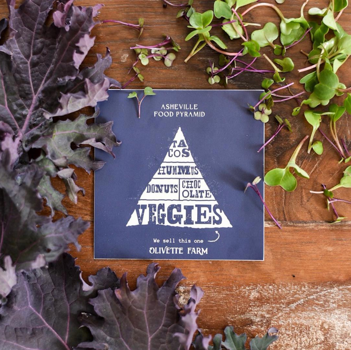 "Asheville NC Food Pyramid design on navy sticker in creamy tan ink for Olivette Farm, textured illustrated print reads: ""tacos, hummus, donuts, chocolate, and veggies,"" created by freelance artist Russell Shaw, with greens and vegetables around edges on table."