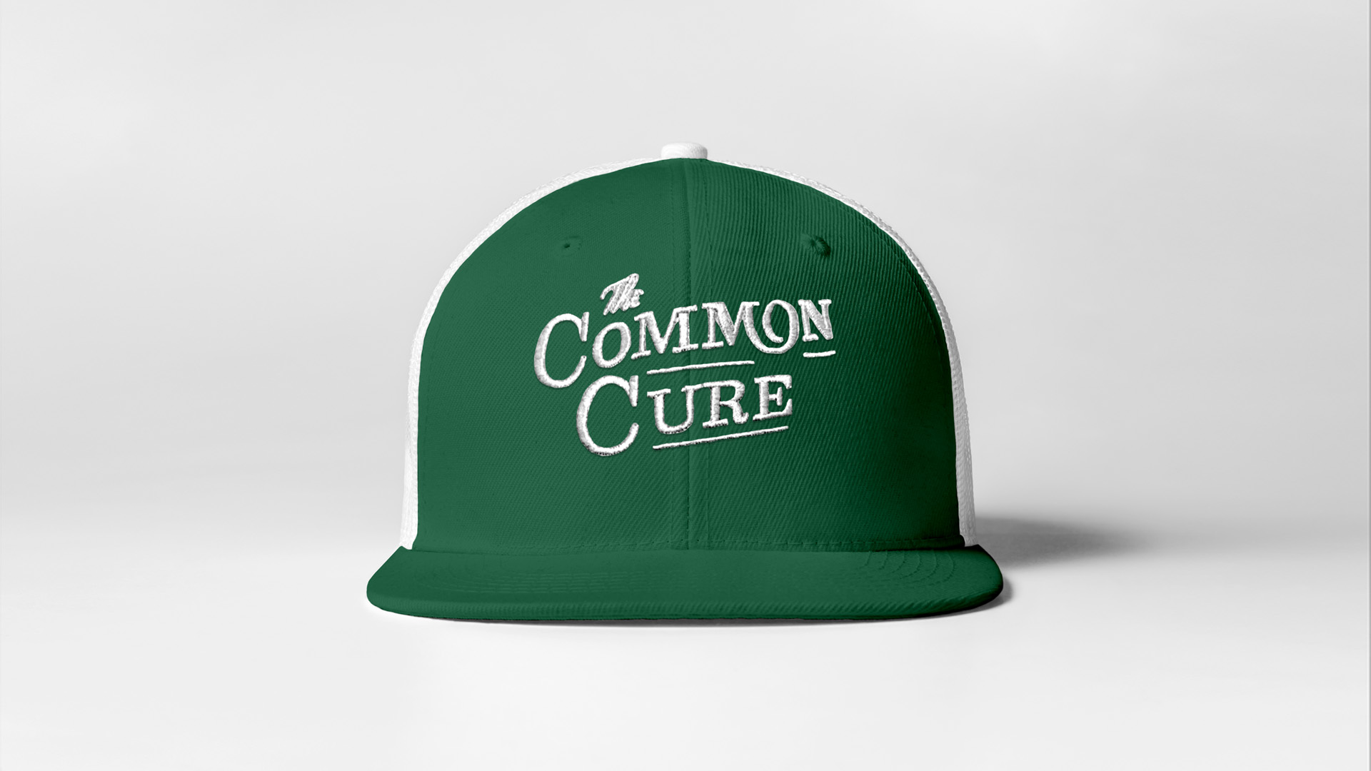 The Common Cure hat design as part of the brand identity collateral. Green front, white back, trucker hat with emroidered logo.