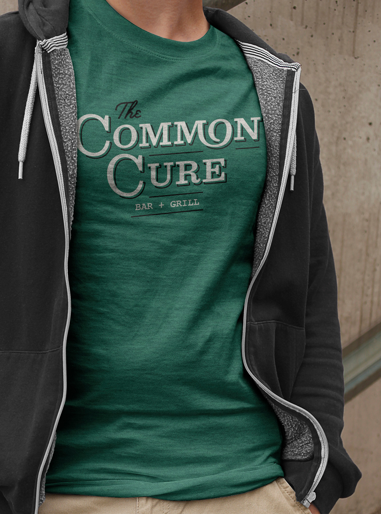 Front of shirt and apparel design for the common cure, with the logo across the chest, heathered textured green shirt, on man in hoodie.