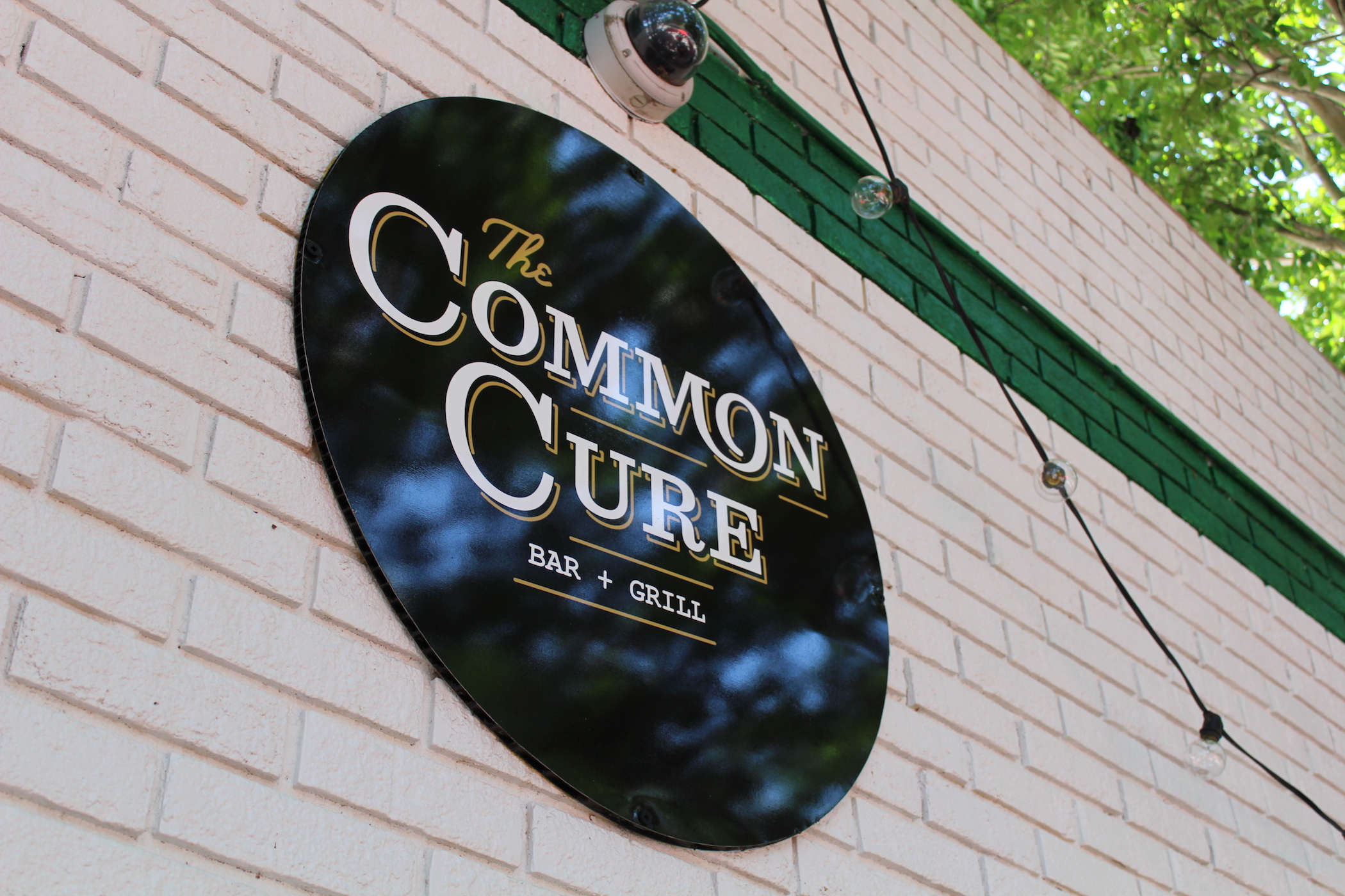 Exterior wall sign for the restaurant shows the logo in white and gold on a black circular sign, painted white brick with a painted green stripe, designed by Russell Shaw.