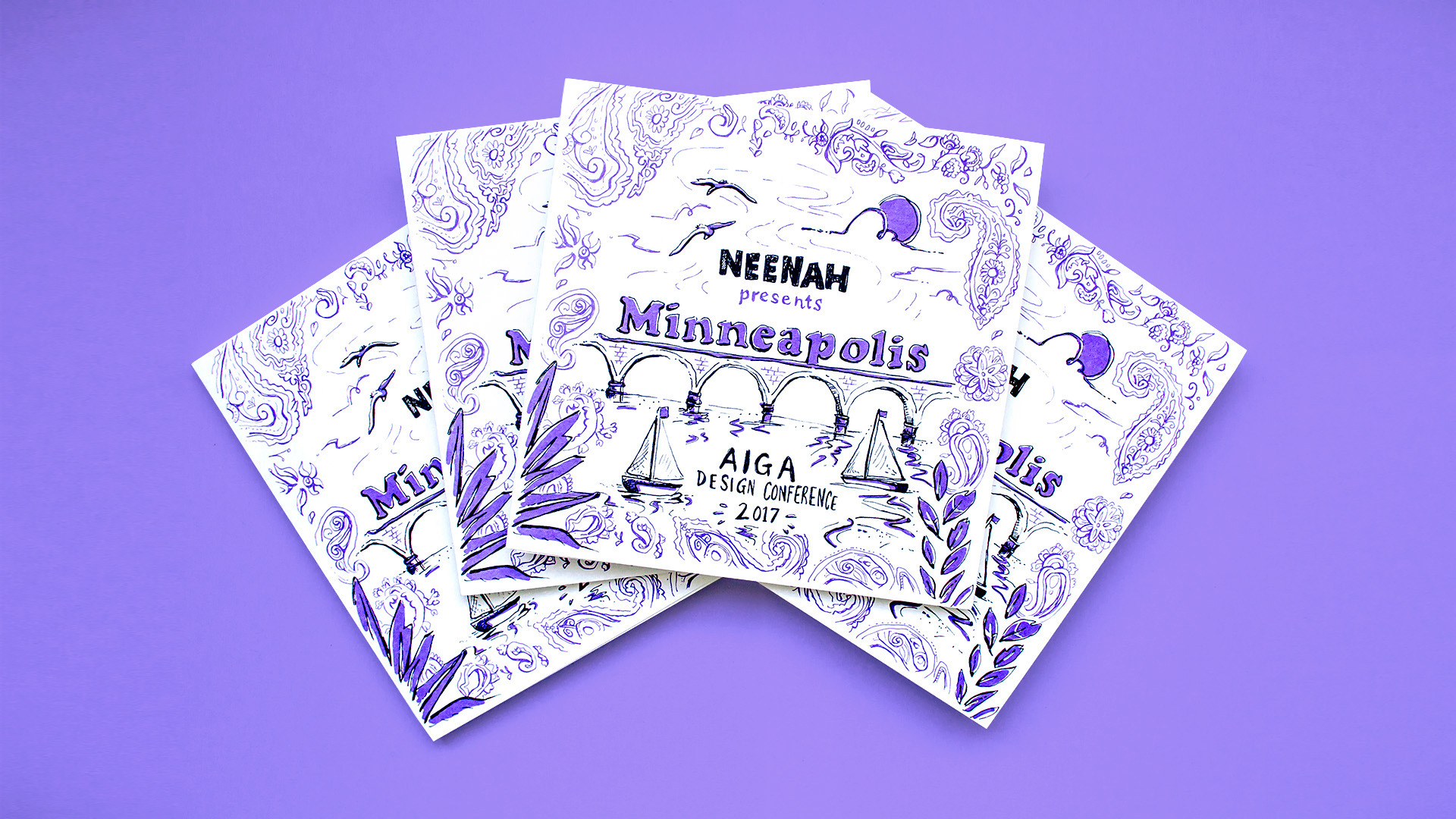 Front covers of the Neenah Presents Minneapolis AIGA Design Conference 2017 promotional piece of hand drawn and illustrated city maps, fun facts, and neighborhood guides. Cover shows: paisley patterns in purple, stone arch bridge, and boats.