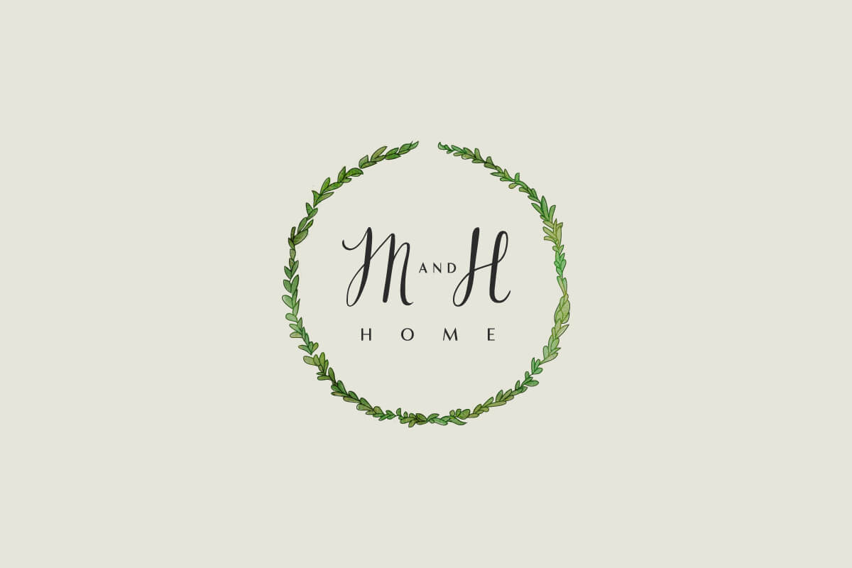 Milk and Honey Home interior designer logo with calligraphy letters in the center of a laurel wreath