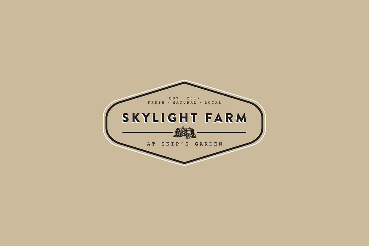 Skylight Farm logo design with a tractor in the middle of a label