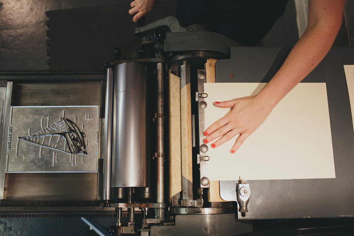 A woman runs the sailboat illustration plate through the letterpress and onto the thick duplex cream colored cotton linen paper.