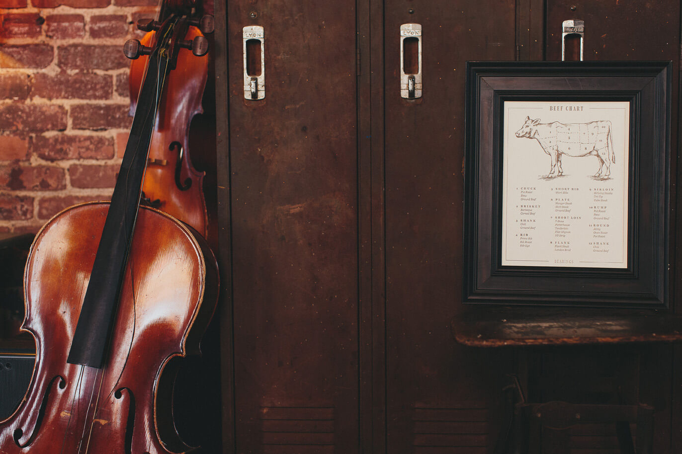 Hand drawn illustrated fine art print diagram of types of cuts of beef is framed in a dark wood frame and sits in front of lockers and next to an old violin.