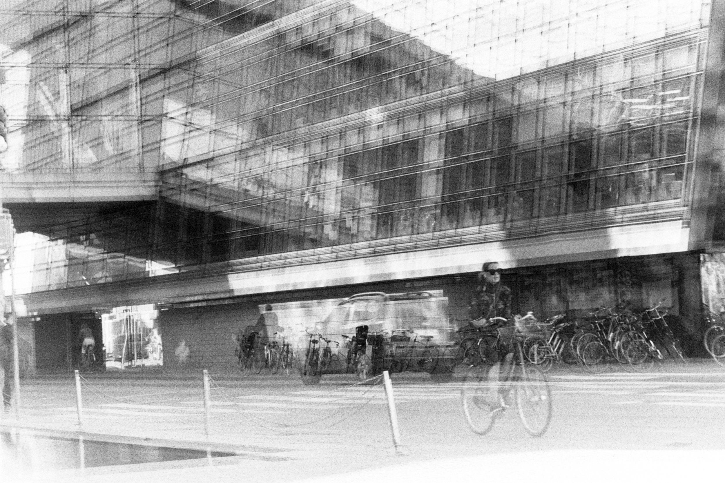 Copenhagen, Denmark.  Double exposure. Waiting for the right moments. Taken in the middle of the day sheltered by the subject building. Creating some pattern with a double exposure slightly off with the 2nd frame.