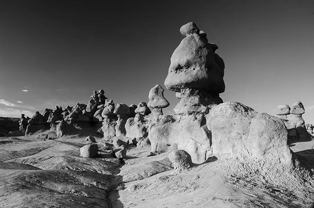 2018.52- Goblin Valley. . . Nature has a funny way of doing things sometimes. While we mostly only notice when it's destroying homes, roads and lives - we can stop to admire its creativity as well.  This was at one point the coast of an ancient sea.  Erosion caused lower layers of soft sandstone to erode and leave behind these mushroom capped little goblins. . . #erosion #climatechange  #blackandwhitephotography  #goblinvalley  #nikonimages @nikonphotocontest  @nikonusa