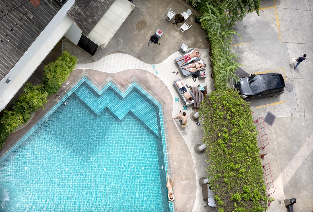 Bangkok, Thailand.  Western tourists trying to get some sun in the rainy season, a very hot, humid but cloudy period.