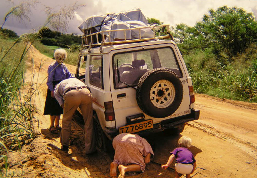 Me (on the right) helping fix our broken down car on a trip through the Serengeti. My grandmother supervising.