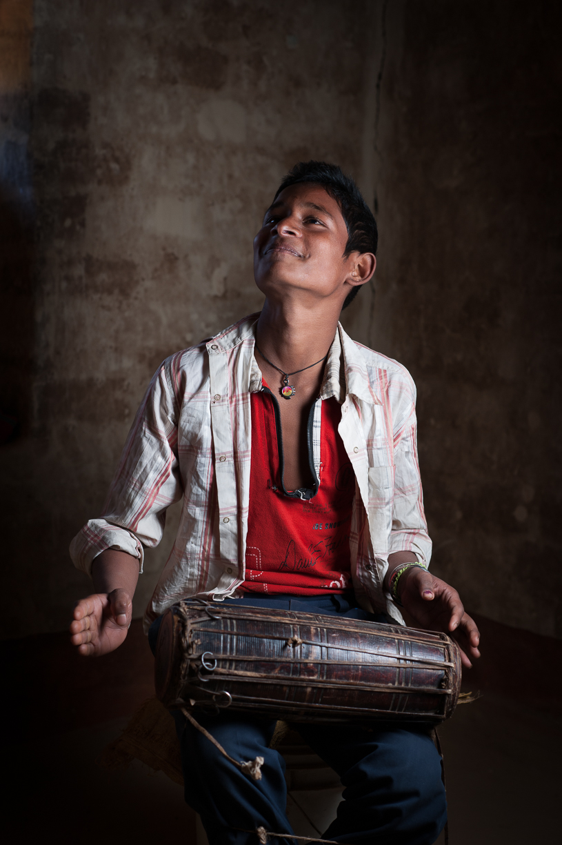 This is his son who is carrying on the Gandharba tradition by playing the drum. I knew I wanted to photograph him because he lights up while performing. Most Gandharba children are not learning to play instruments anymore.