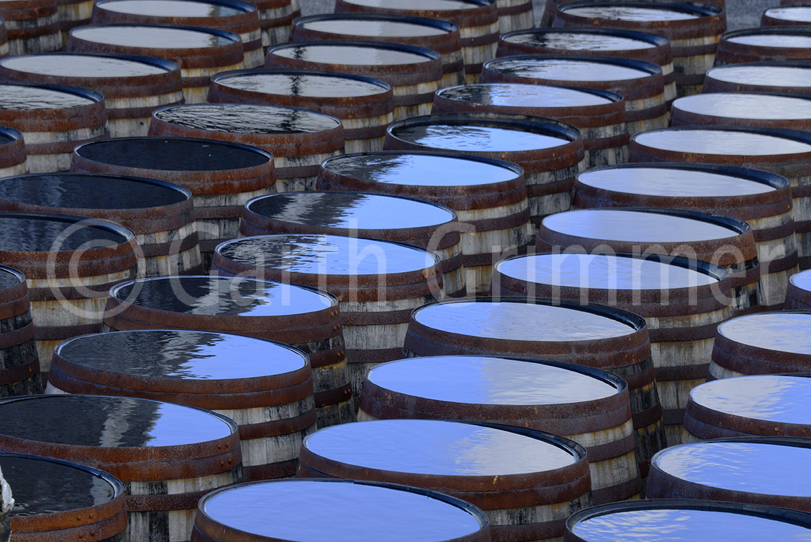 Sky reflected in rain on top of scotch whiskey barrels