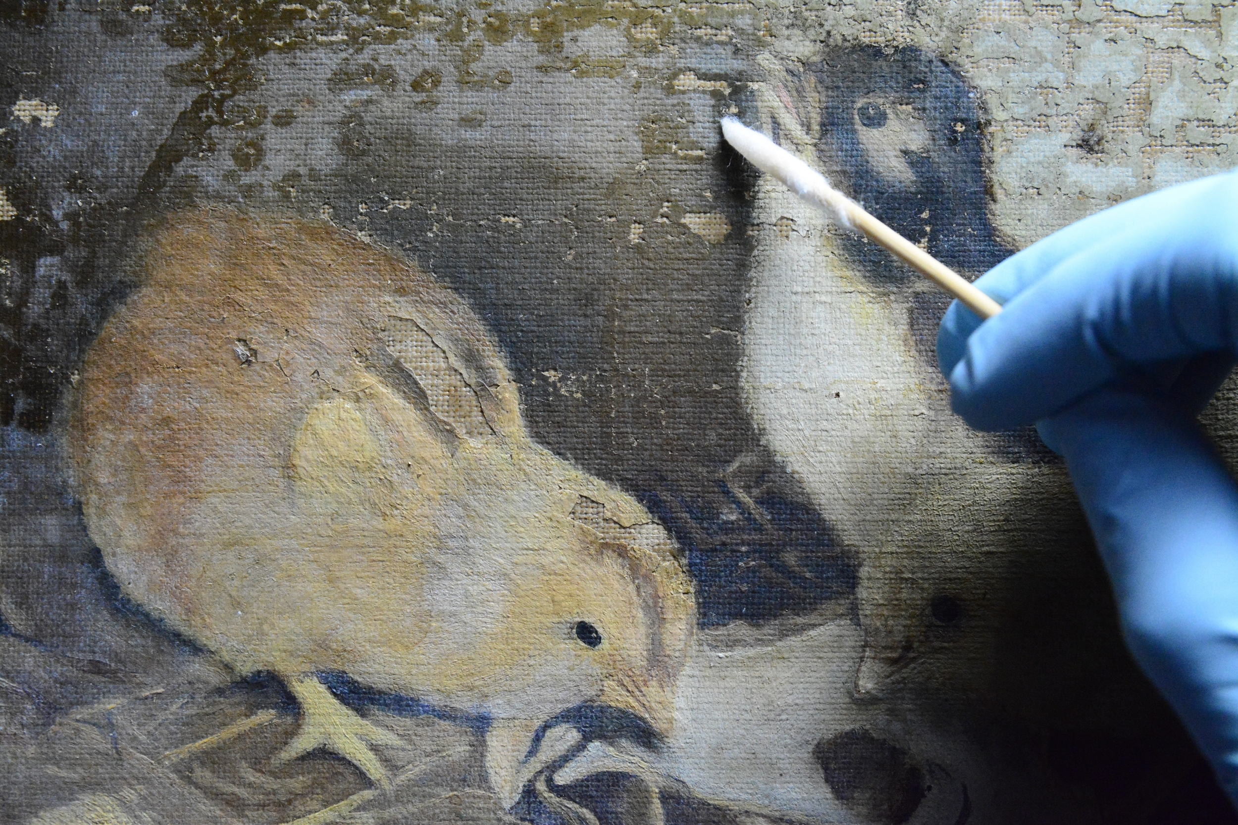 During the removal of excess adhesive from the surface of the painting.