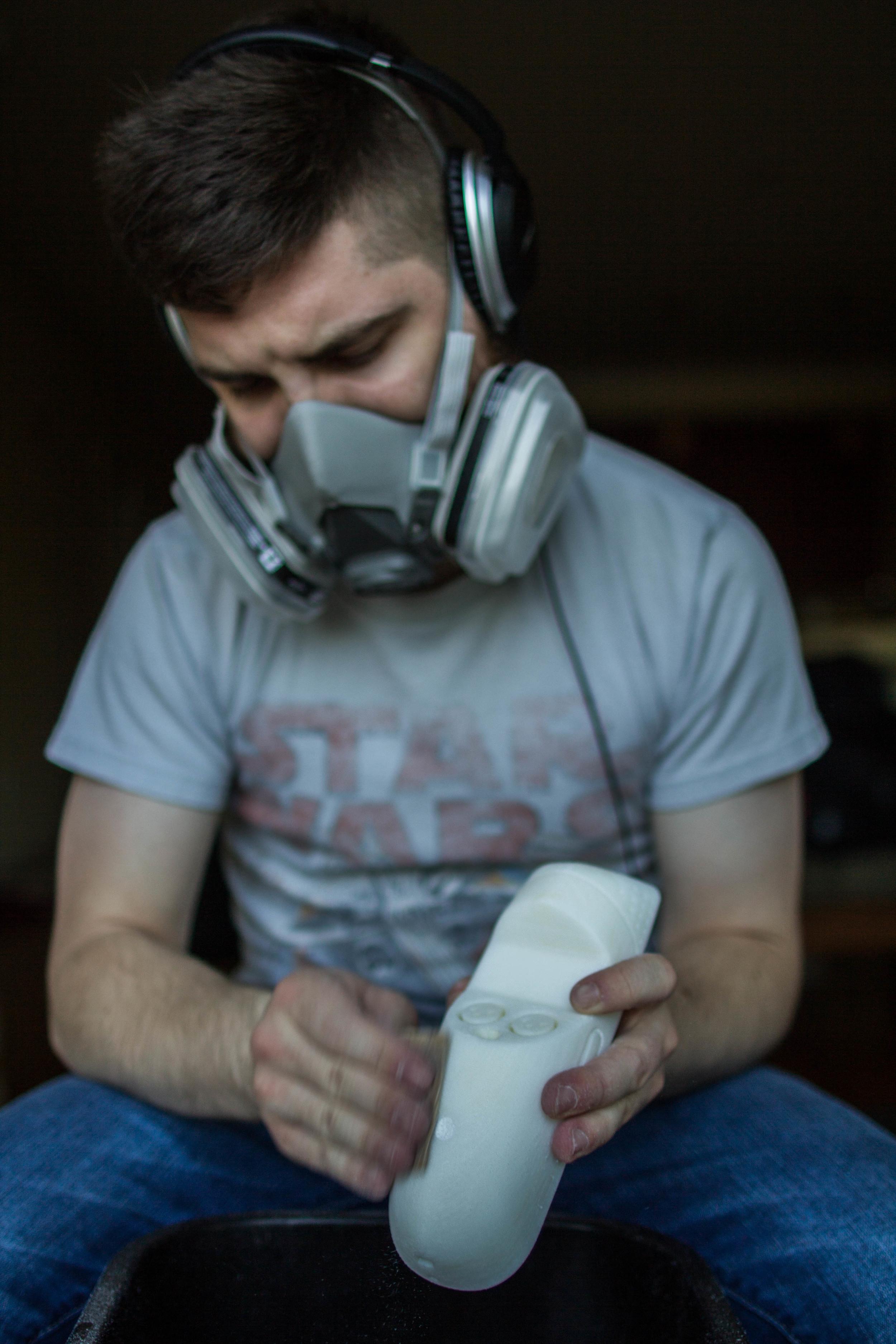 Designer Colin Beney sanding the 3-D printed prototype.