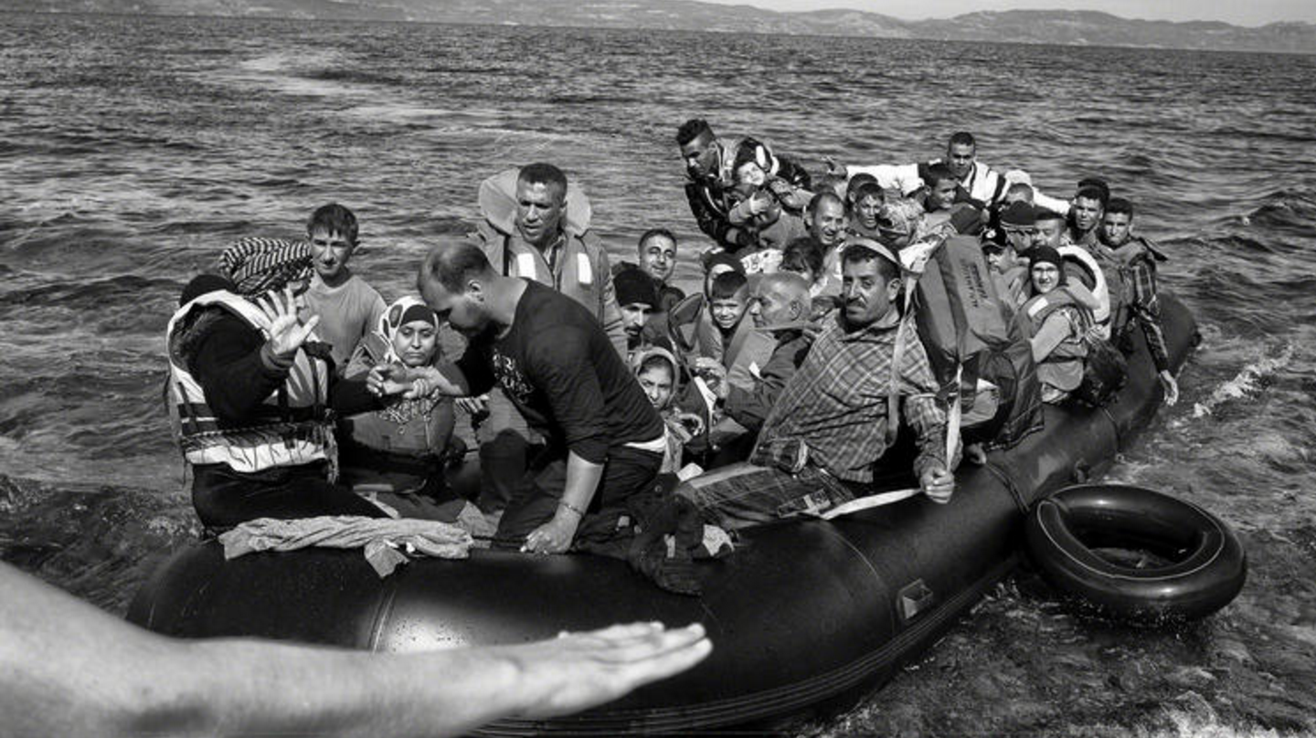 A rubber boat packed with refugees and migrants lands on the shoreline of Lesbos after successfully crossing the Aegean Sea from Turkey in 2015.  (Tom Stoddart)