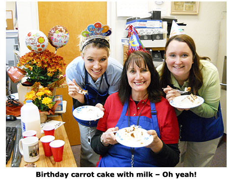 Nicole Hoff and Maya Roberts present Marie Goe with carrot cake