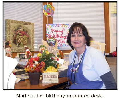 Marie enjoys her autumn-themed birthday presents at her desk at Southgate Coins