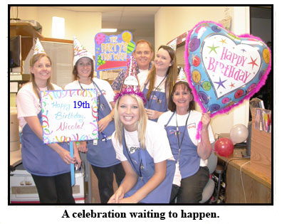Southgate Coins employees pose with birthday signs and balloons