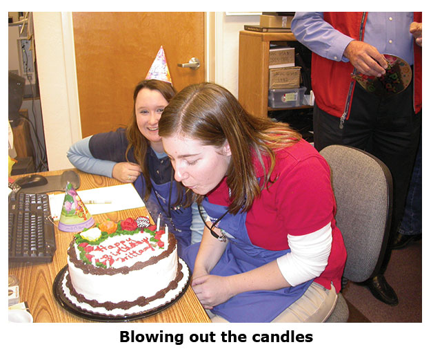 Brittany blows out candles at her coin shop birthday party