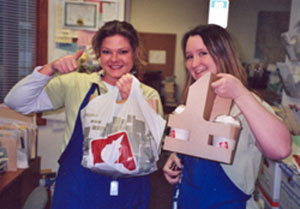 Southgate Coins employees Amy and Maya retrieve Free Lunch Friday food