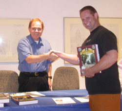 Rusty Goe hands out a signed copy of his new James Crawford