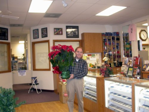 Southgate Coins owner Rusty Goe poses with poinsettias.