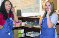 Southgate Coins employees Heather and Sara install new shelves for inventory