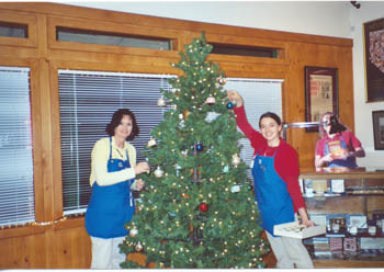 Southgate Coins owner Marie and employee Somer put up the Christmas tree