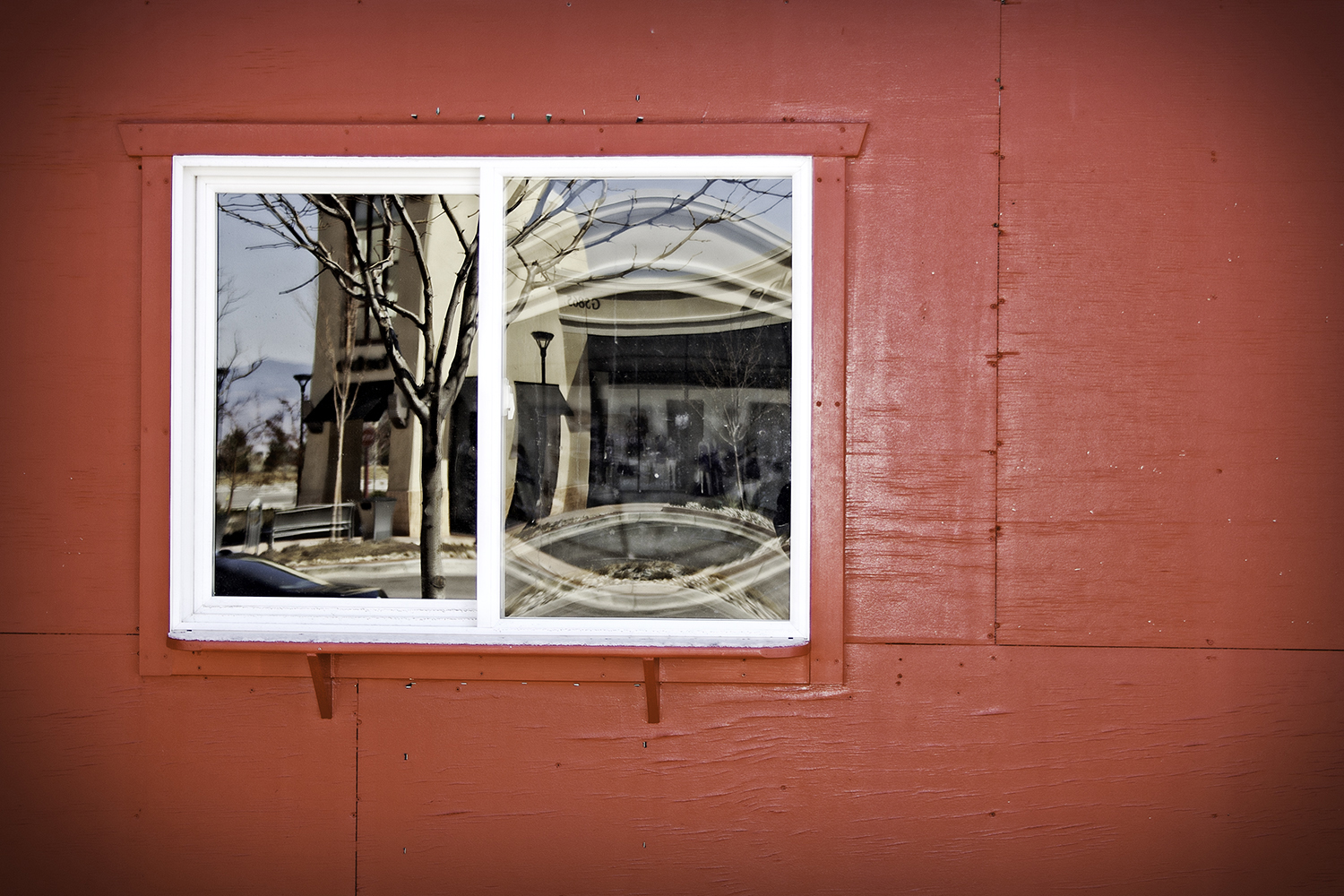 Reflection of the Bebe store against a fairly intense red wall.  Outdoor shops at Centerra, Loveland, Colorado.
