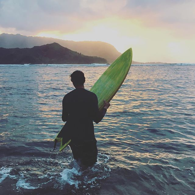 A handsome surfer paddles out to the surf break at sunset in Hanalei Bay on Kauai, Hawaii –– where Laird Hamilton resides.