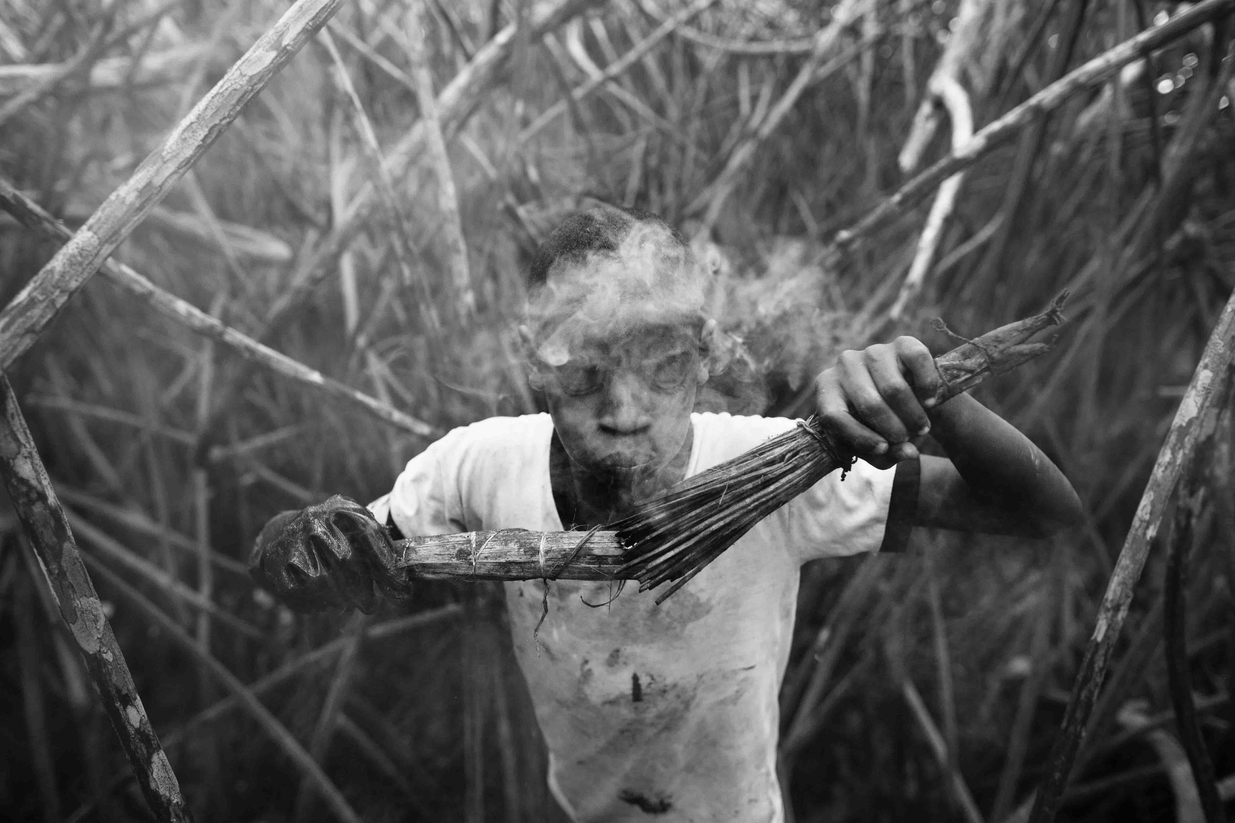 Jefferson Muñoz lights blows into a torch made out of coconut husks. The torches blow smoke for hours repelling the vicious mosquitoes and black flies of the mangrove. Bug spray only repels insects for a few minutes after application. 2014.
